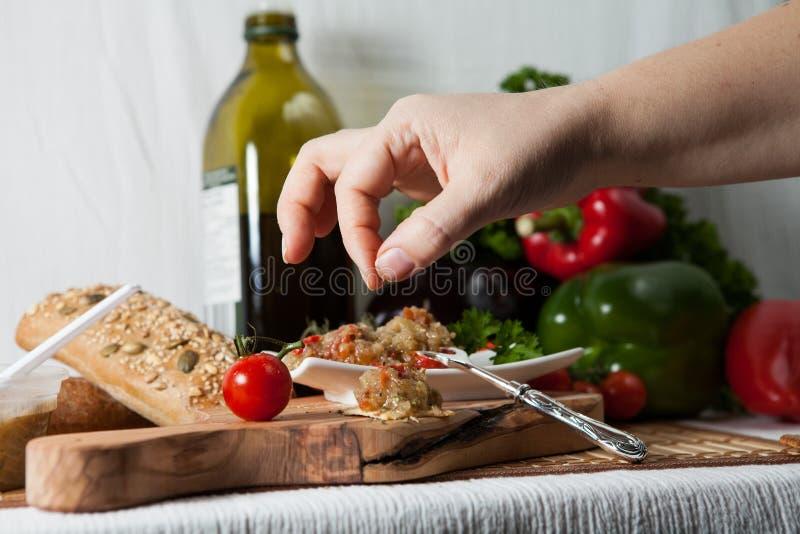 De vrouw voegt een snuifje van zout op de heerlijke auberginesalade toe royalty-vrije stock fotografie