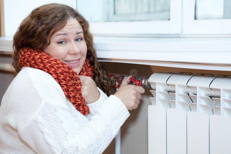 De vrouw voelt koud wanneer de draaiende thermostaat van centrale verwarming bedriegt stock fotografie