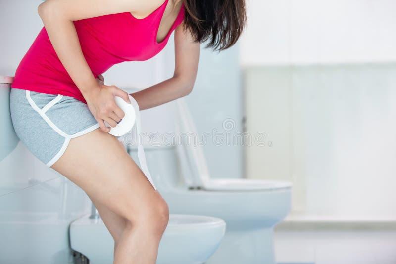 De vrouw voelt pijn met constipatie stock afbeeldingen