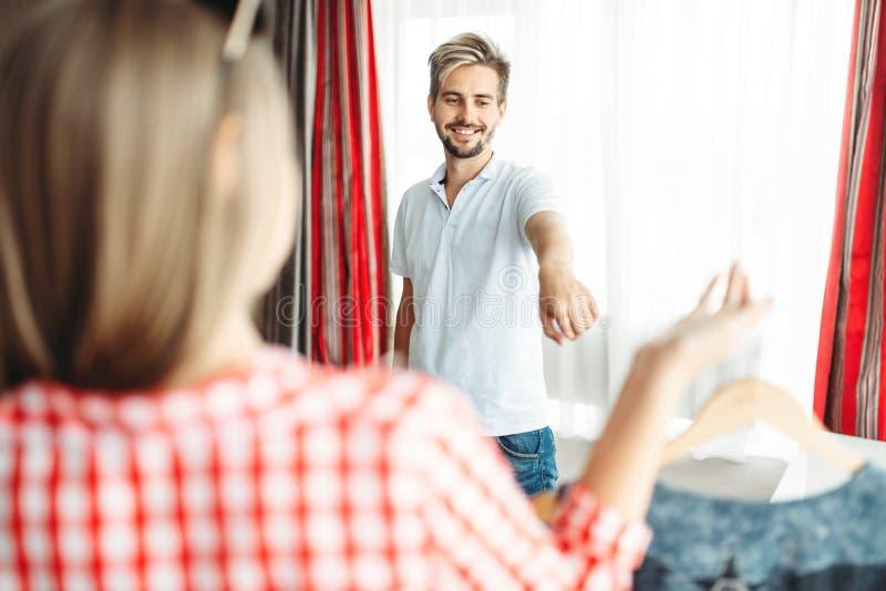 De vrouw vraagt echtgenoot welke kleding om een reis over te nemen stock afbeelding