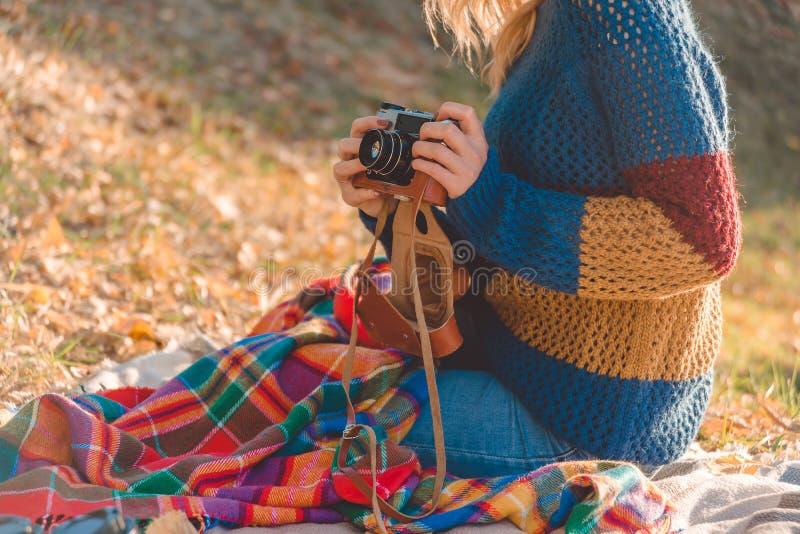 De vrouw in warme sweater zit op kleurrijke plaid en houdt retro uitstekende camera royalty-vrije stock fotografie