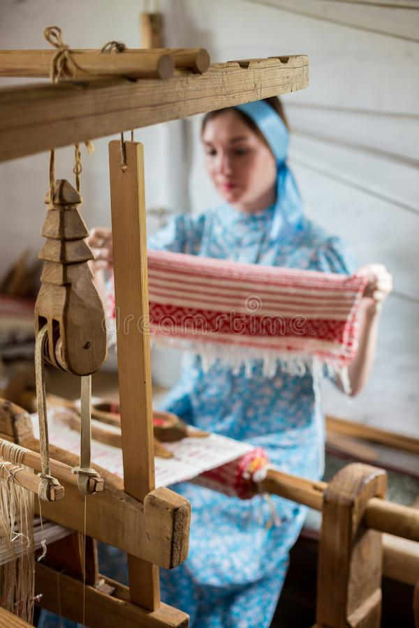 De vrouw weeft de kleurrijke katoenen robe of kleedt zich door houten weefgetouw in het lokale dorp in Rusland te gebruiken stock foto