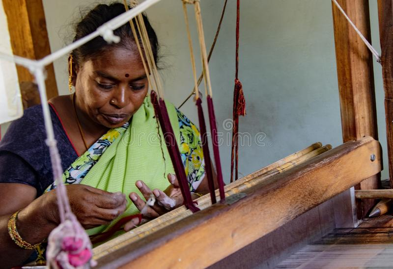 De vrouw weeft stof op een traditioneel weefgetouw royalty-vrije stock afbeelding