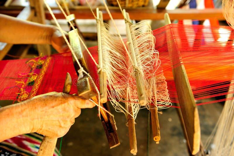 De vrouw weeft textiel met weefgetouw royalty-vrije stock afbeeldingen