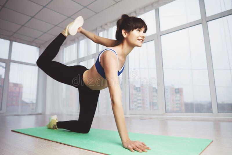 De vrouw werkt het uitvoeren van statische uitrekkende oefening uit stock foto's