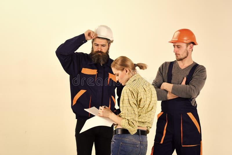 De vrouw wijzigt plan van reparatie Misverstandconcept Brigade van arbeiders, bouwers in helmen, herstellers, dame het debatteren stock fotografie