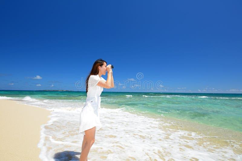 De vrouw in witte kleding kijkt op zee stock afbeelding