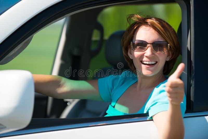 De vrouw in witte nieuwe auto bij aard met duimen ondertekent omhoog