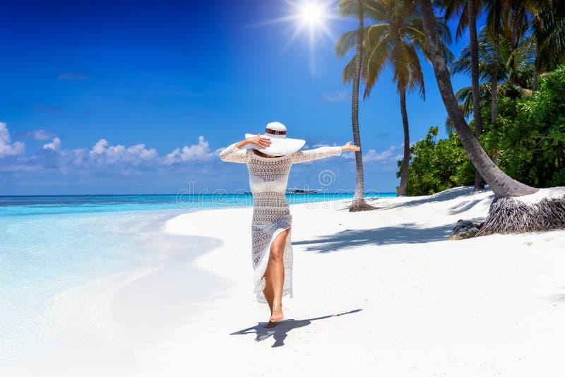 De vrouw in witte de zomerkleding geniet van haar vakantie in de Maldiven stock afbeeldingen