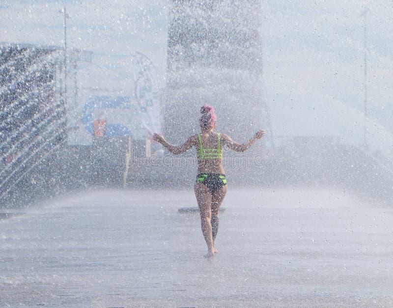 De vrouw wordt gekoeld onder de stralen van de fontein stock foto