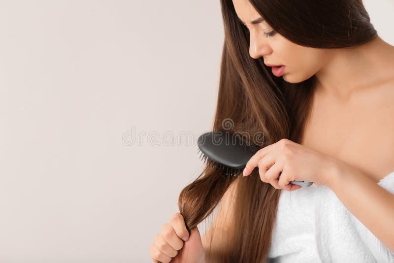 De vrouw worstelt om haar haar op lichte achtergrond te borstelen royalty-vrije stock afbeeldingen