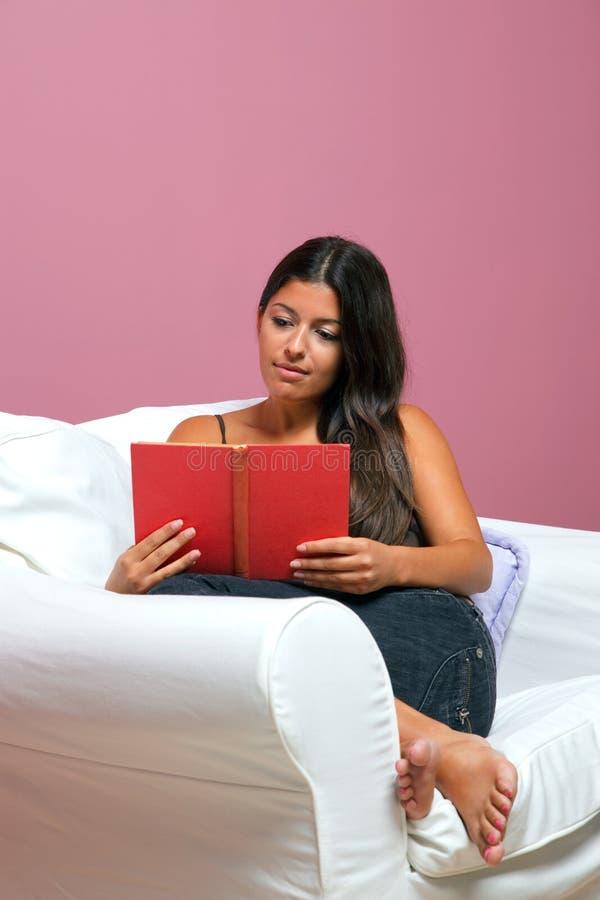 De vrouw zat in een leunstoel lezend een boek royalty-vrije stock foto