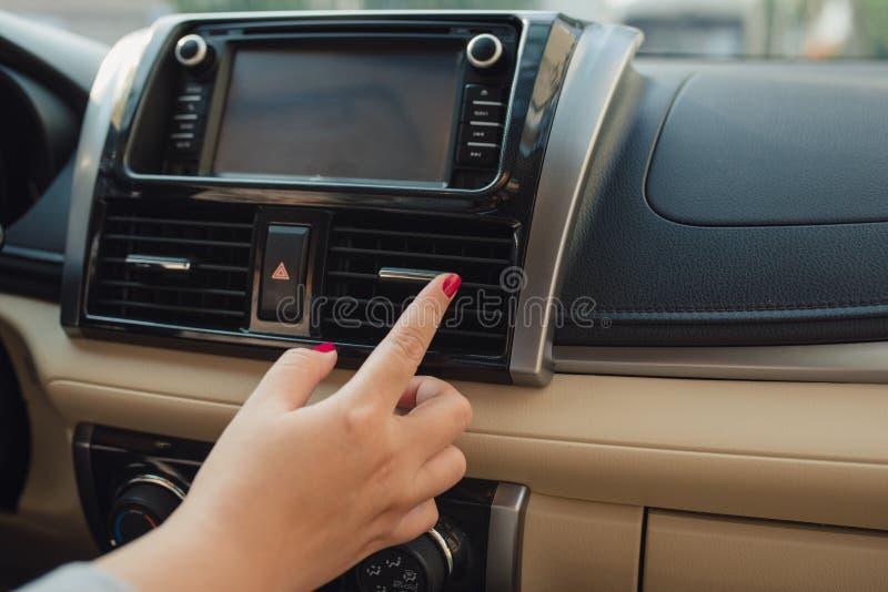 De vrouw zet airconditioning in de auto aan Modern autobinnenland royalty-vrije stock foto