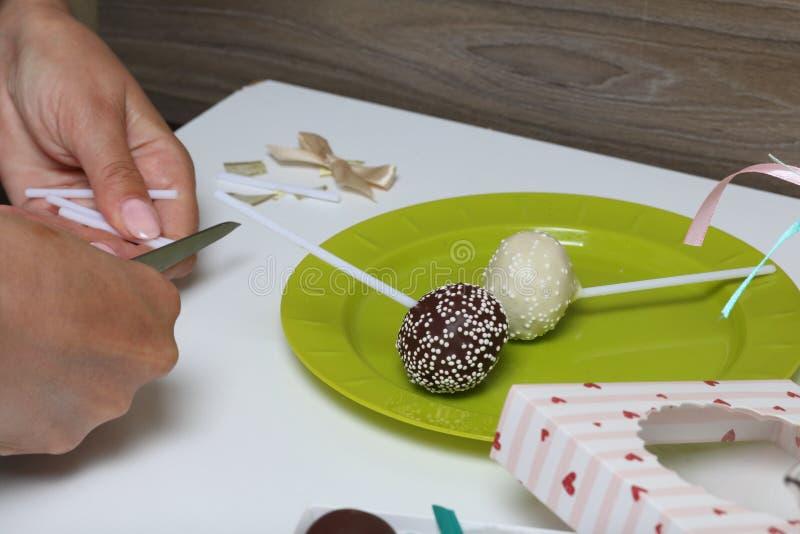 De vrouw zet cake knalt in een giftdoos Het suikergoed van het schaartoverstokje stock afbeelding