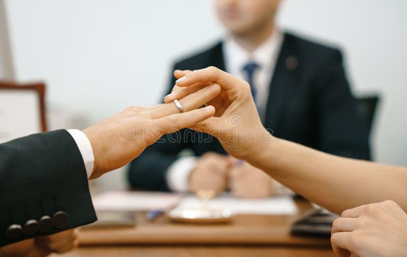 De vrouw zet een trouwring in een registratiebureau voor een man Huwelijk en handenclose-up tegen de achtergrond van de ceremonie royalty-vrije stock foto