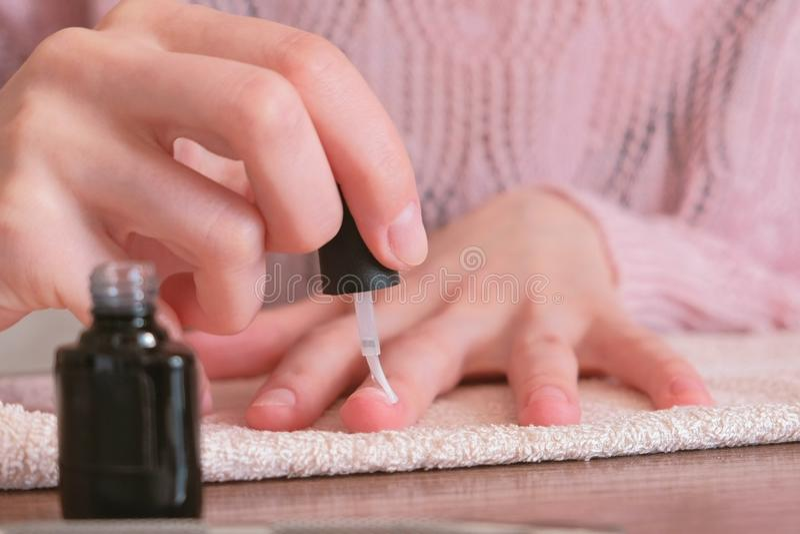 De vrouw zet inleiding op haar spijkers alvorens schellak te zetten Close-uphanden stock foto