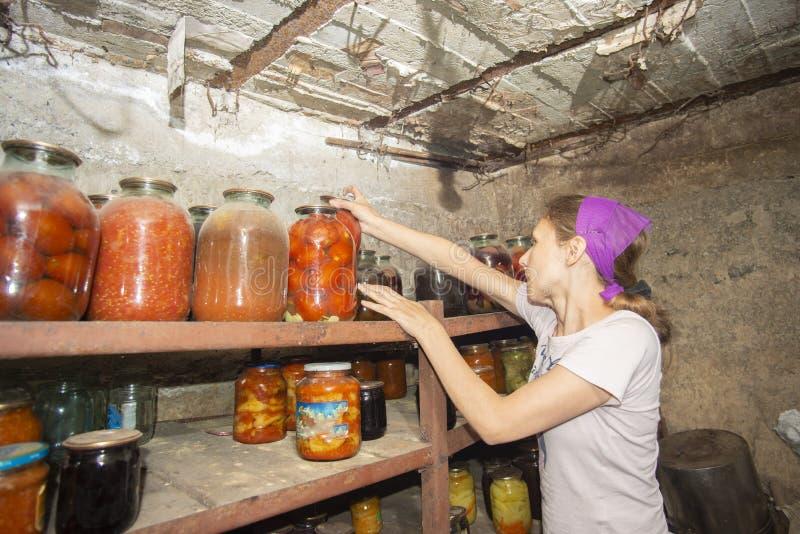 De vrouw zet kruiken met groenten en vruchten in de kelderverdieping met voedsel, lange tijd voor opslag stock afbeelding