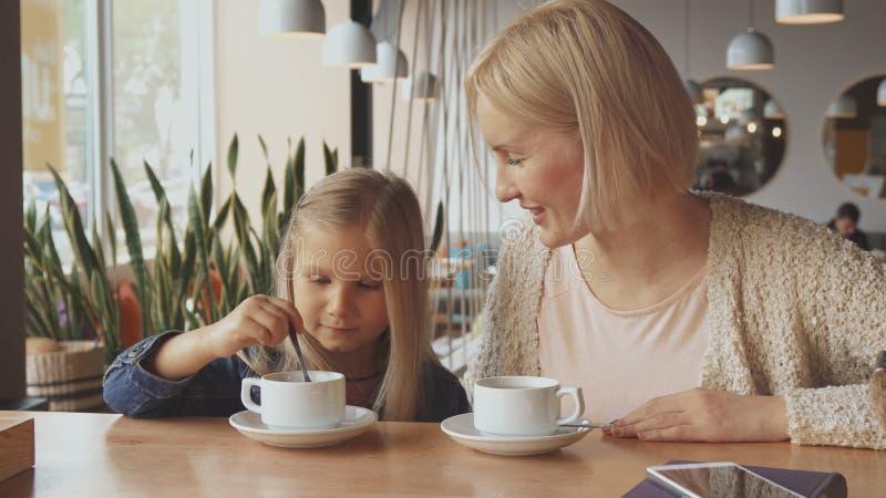 De vrouw zet lepel in de dochter` s kop bij de koffie stock foto