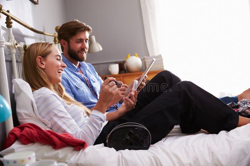 De vrouw zet op omhoog maakt aangezien de Mens Digitale Tablet in Slaapkamer gebruikt royalty-vrije stock foto's