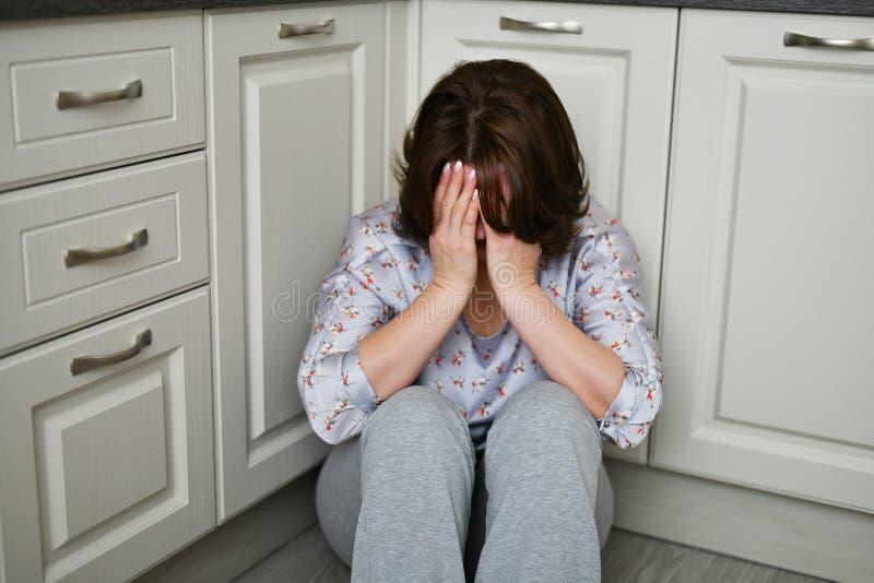 De vrouw zit bij de keukenvloerbedekking haar gezicht met haar handen Depressie, zorg of frustratie royalty-vrije stock fotografie