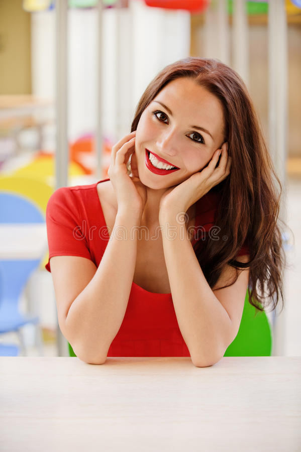 De vrouw zit bij weinig lijst in koffie royalty-vrije stock fotografie