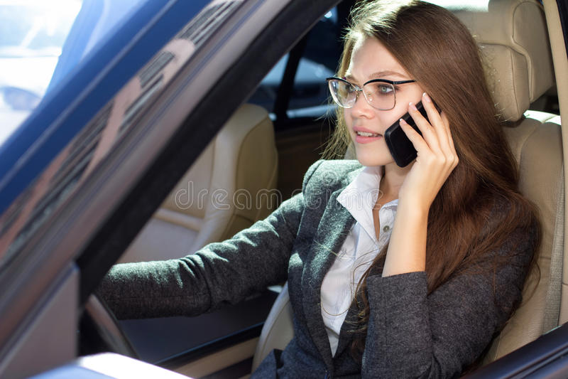 De vrouw zit in de auto en spreekt telefonisch stock foto's