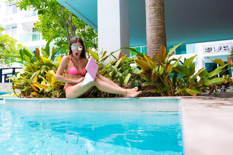 De vrouw zit door de pool en laat vallen laptop in het water Het meisje rust op een minicomputer Selectieve nadruk stock fotografie