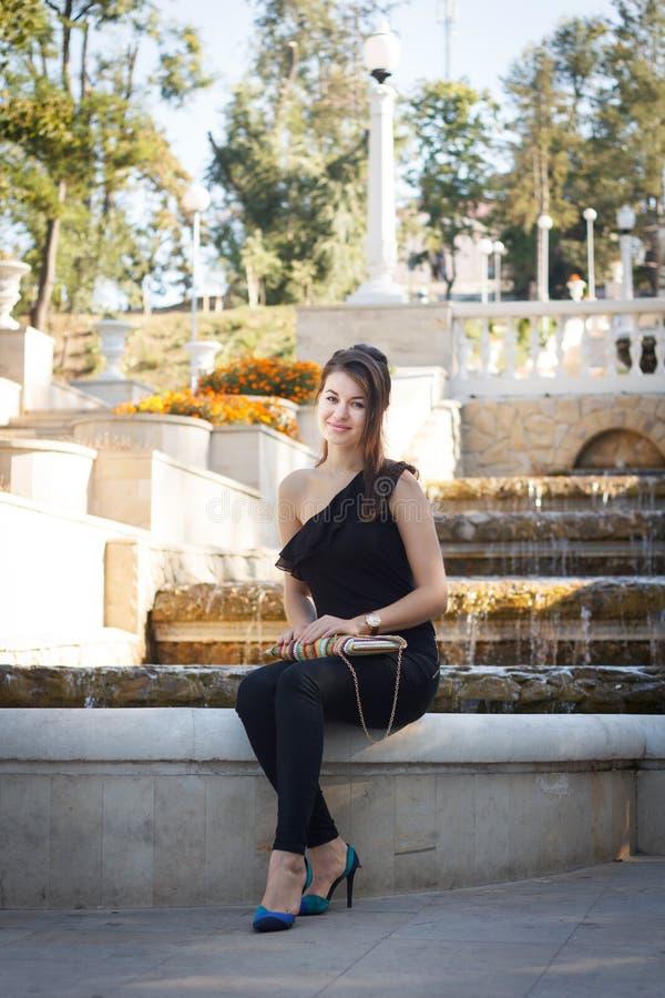 De vrouw zit en heeft een rust op rand van fontein royalty-vrije stock foto