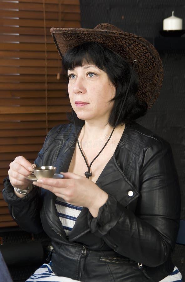 De vrouw zit in koffie met een kop stock fotografie