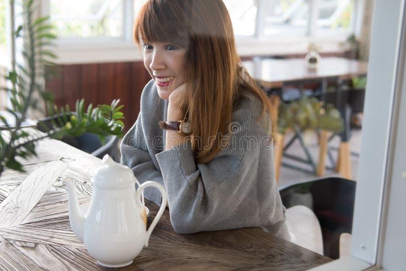 De vrouw zit in koffie met hete thee tijdens brunch het Aziatische wijfje heeft stock fotografie