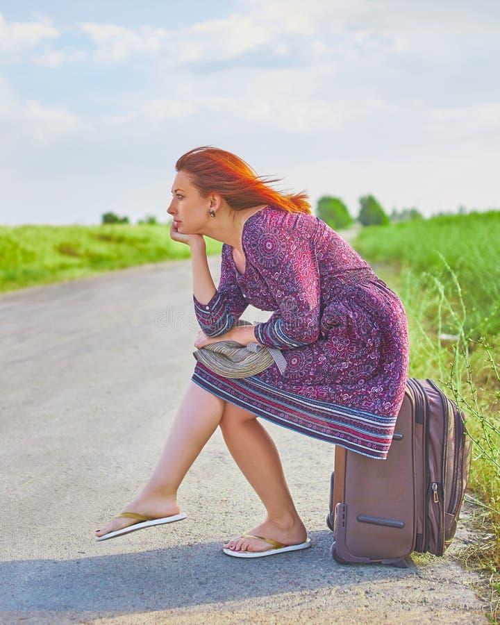 De vrouw zit op bagage royalty-vrije stock foto's