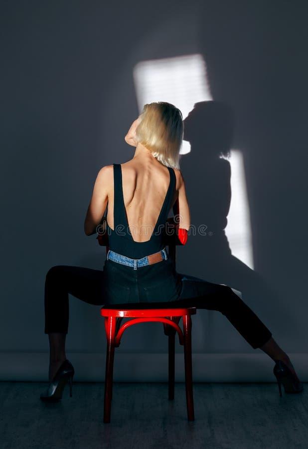 De vrouw zit op een rode stoel; blauwe achtergrond stock foto's