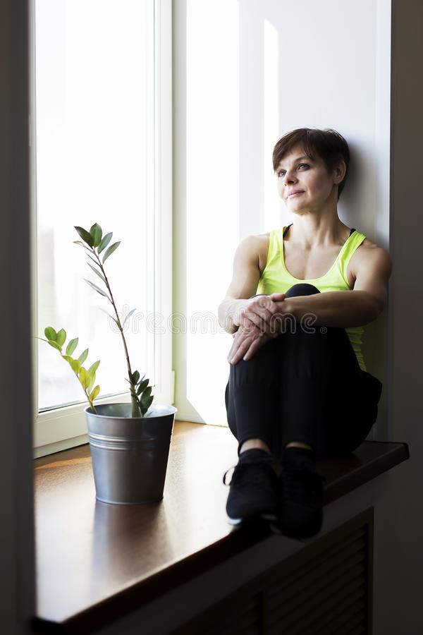 De vrouw zit op een venster die na een training rusten royalty-vrije stock foto's
