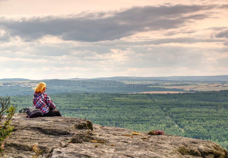 De vrouw zit silhouet in bergen, zonsondergang en dalingslandschap Vrouwelijke wandelaar die over rand mooie Zonsondergang bekijk stock afbeeldingen