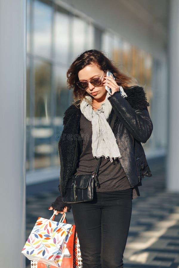 De vrouw in zonglazen een zwart leerjasje, zwarte jeans met het winkelen doet het spreken op mobiele telefoon voor weerspiegelde  royalty-vrije stock foto