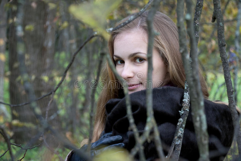 De vrouw in Zwarte Bontjas kijkt door Autumn Branches stock fotografie