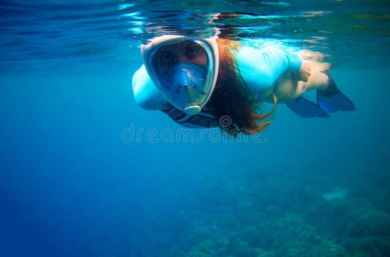 De vrouw zwemt in blauwe overzees Meisje die in volledig-gezichtsmasker snorkelen Snorkel close-up onderwaterfoto Snorkelend onde stock fotografie