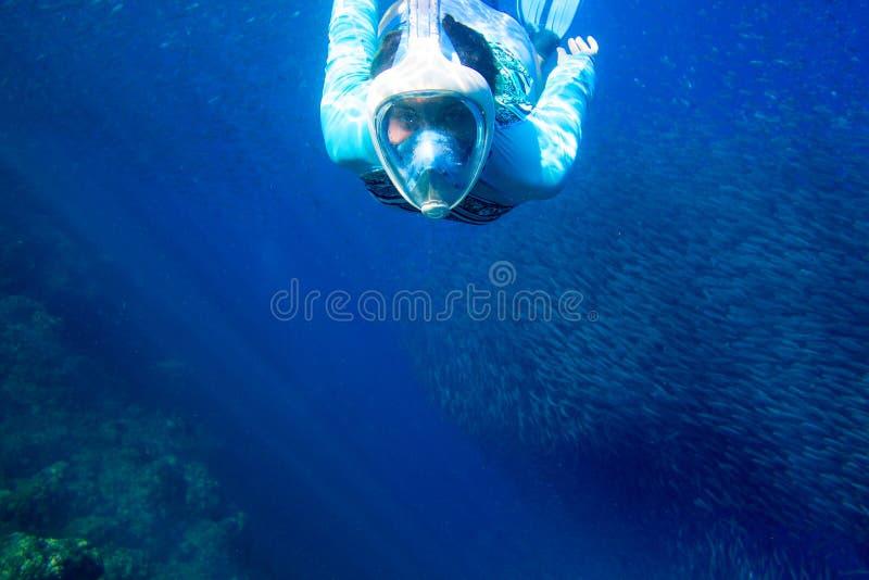 De vrouw zwemt met vissenschool Meisje die in volledig-gezichtsmasker snorkelen Snorkel met de onderwaterfoto van de vissenkoloni stock afbeelding