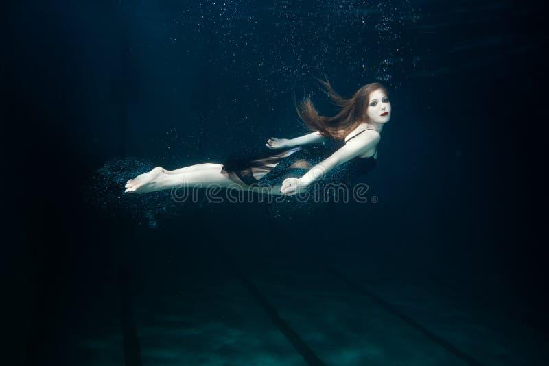 De vrouw zwemt onderwater stock afbeelding