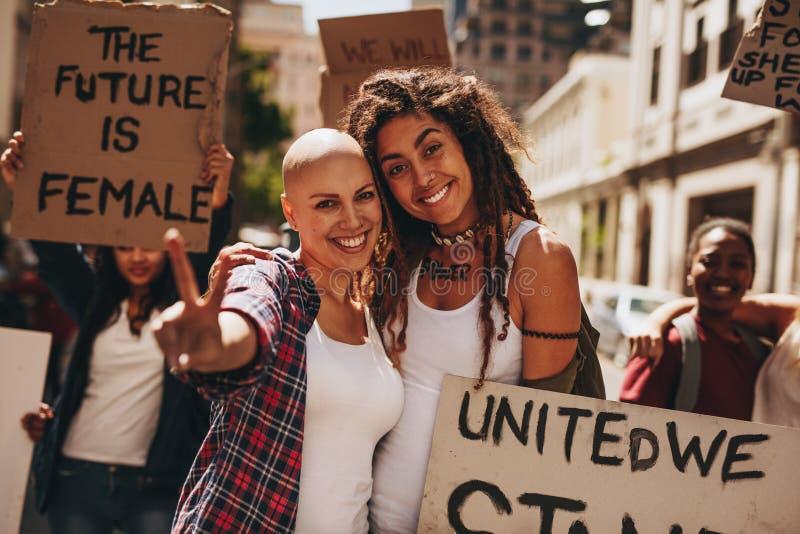 De vrouwelijke activisten met aanplakbiljetten en de vrede ondertekenen royalty-vrije stock foto's