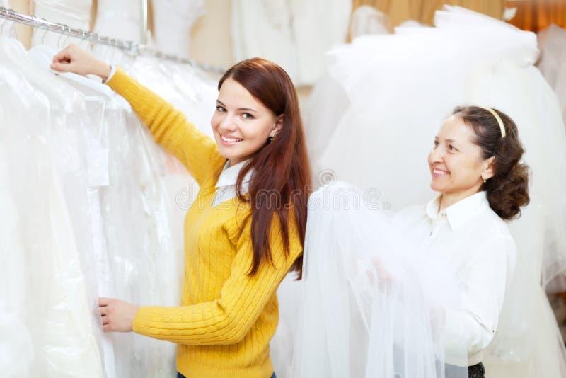 De vrouwelijke adviseur helpt bruid bij winkel stock foto's