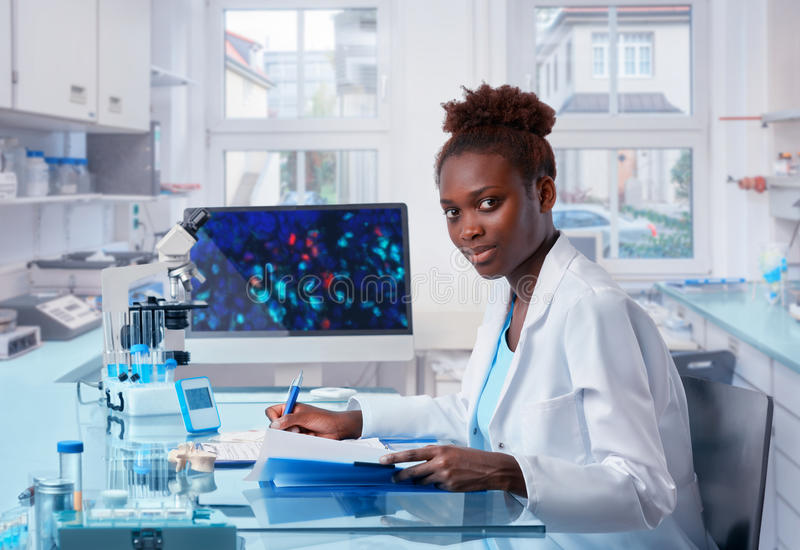 De vrouwelijke Afrikaanse wetenschapperwerken in modern biologisch laboratorium stock fotografie