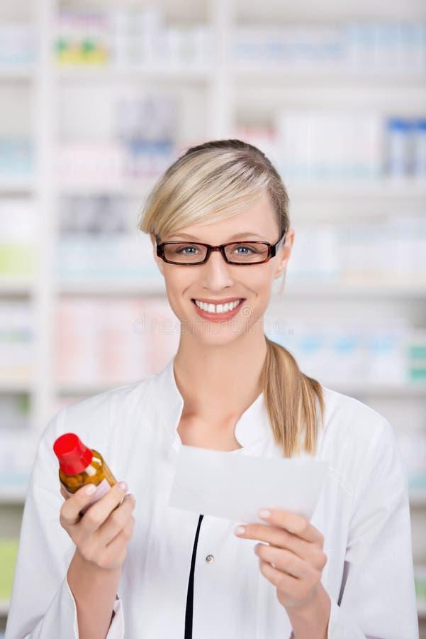 De vrouwelijke apotheker houdt voorschrift en geneeskunde royalty-vrije stock fotografie