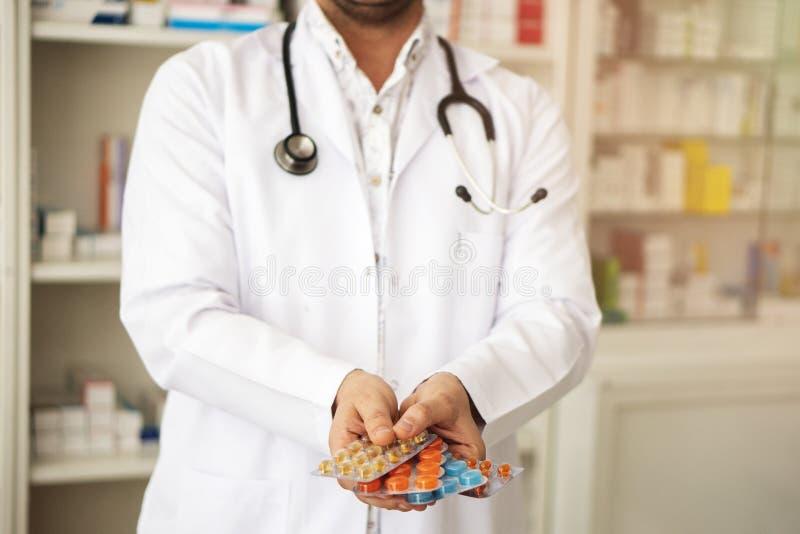 De vrouwelijke apotheker is ter beschikking bedrijfsdossiers, geneeskundekabinetten op achtergrond stock afbeeldingen