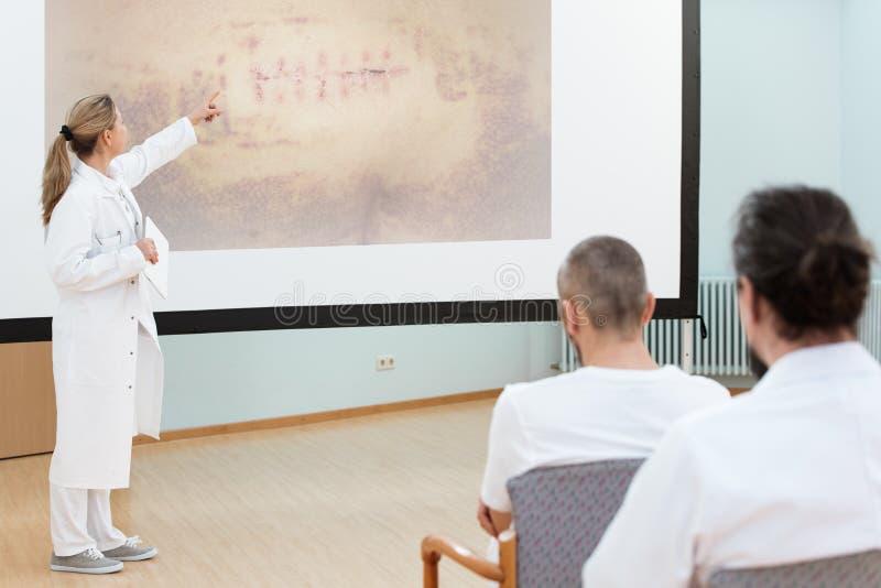 De vrouwelijke arts geeft een briefing of een lezing aan medisch personeel stock fotografie