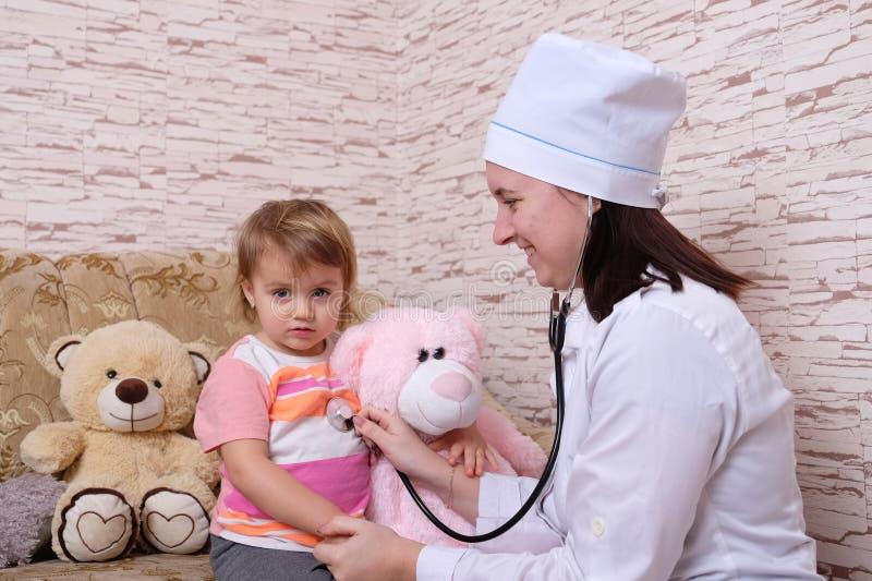 De vrouwelijke arts luistert thuis aan kind met stethoscoop stock afbeeldingen