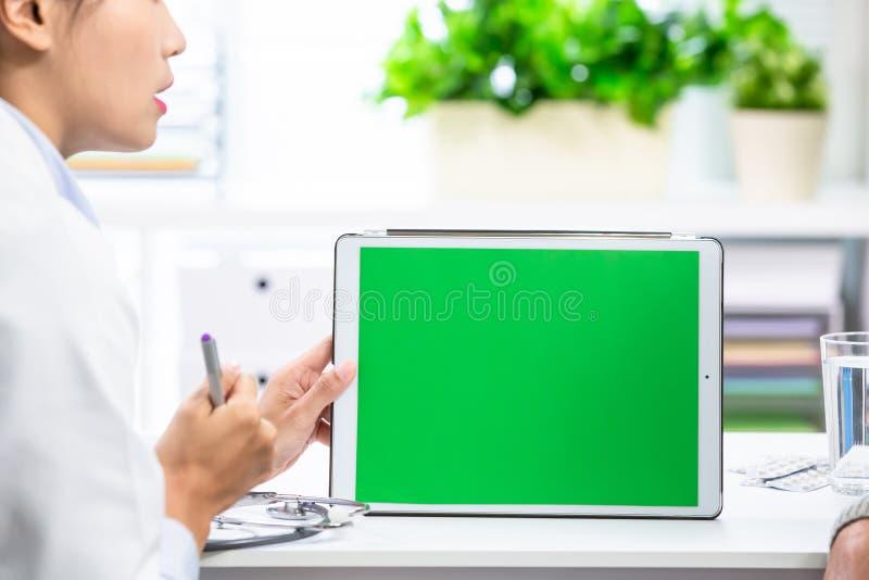 De vrouwelijke arts verklaart met tablet stock foto