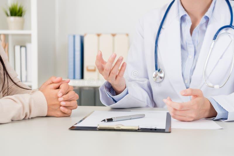 De vrouwelijke arts verklaart de oplossing van de ziektebehandeling stock afbeelding