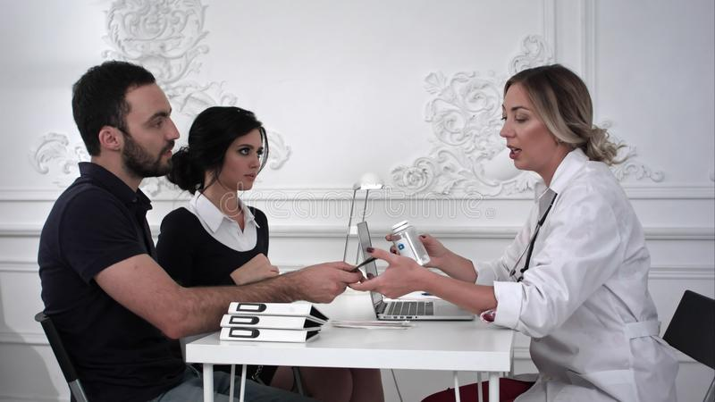 De vrouwelijke arts verkoopt de pillen aan familiepaar in het bureau royalty-vrije stock fotografie
