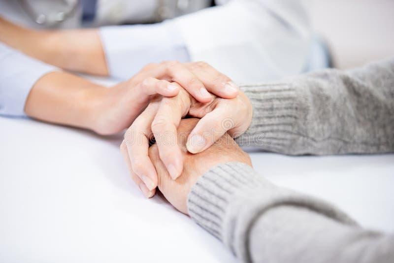 De vrouwelijke arts ziet oudere patiënt stock foto's